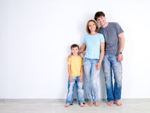 Family standing together near the empty wall Royalty Free Stock Images