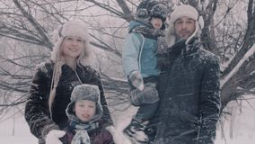 Family standing under snowfall. Two boys and there parents. 4K stock video footage