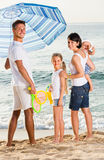 Family  standing  under sun umbrella Stock Images