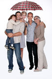 Family standing under umbrella Stock Image