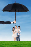Family standing under umbrella at field. Portrait of happy family standing under umbrella on the meadow. Life and family insurance concept Royalty Free Stock Photos