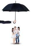 Family standing under umbrella in studio Stock Photos