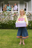 Family standing on veranda overlooking summer garden, focus on girl (4-6) standing on grass with birthday gifts in foreground, smi Royalty Free Stock Photos