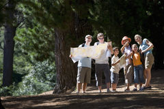 Family standing in woods looking at map Stock Photography