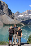 Family stands in front of bow lake with mountain reflection in water Royalty Free Stock Images