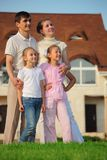 Family stands on grass against house Stock Image
