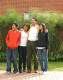Family stands on grass against house Stock Photo