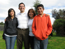 Family stands on grass against house Royalty Free Stock Photo
