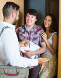 Family stands with realtor in the doorway. Young family stands with realtor in the doorway looking round new flat royalty free stock image