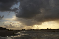 Family in storm. Storm clouds with the sun rising through. Some people walking at the horizon royalty free stock photo