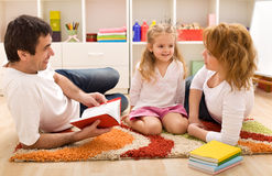 Family story time in the kids room. Happy family reading a story laying on the floor in the kids room Royalty Free Stock Images