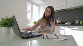 Family stress, multitasking mum with crying infant boy while working on laptop computer and talking on cell phone. Sitting at table in kitchen at home stock footage