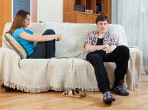 Family stress. Sad guy and girlfriend after quarrel in living room at home stock image