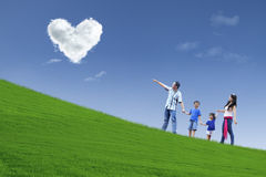 Family stroll in park under heart clouds Stock Images