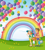 A family strolling with a rainbow and floating balloons Stock Images