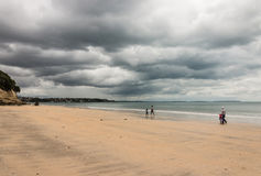 Family strolling on Takapuna beach. In stormy weather Stock Photos