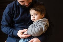 Father holding hand of small pensive boy. Family studio portrait of men and little kid in his hugs. Father holding hand of small boy royalty free stock photos