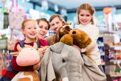 Family with stuffed elephant in toy store playing. Girl sitting on plush toy Stock Photos