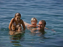 Family in summer fun. Closeup portrait of happy family floating on the clear blue sea and enjoy the summer vacation in Croatia on the Adriatic Sea. A girl stock photo