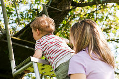Family summer on ladder to tree house Stock Image