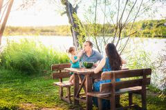 Family in summer on a picnic near a pond, water. Family holiday in nature. A little daughter feeds her father royalty free stock image