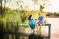 Family in summer on a picnic near a pond, water. Family holiday in nature. A little daughter with her father and a pregnant mothe stock photography