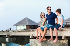 Family on summer vacation. Happy beautiful family of father and kids outdoors on wooden jetty during summer vacation at luxury resort stock image