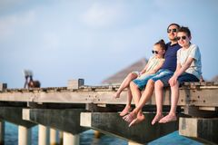 Family on summer vacation. Happy beautiful family of father and kids outdoors on wooden jetty during summer vacation at luxury resort stock photo