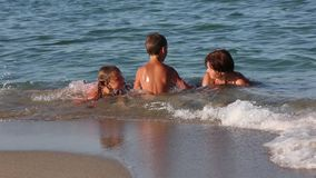 Family Summer Vacation on Sea. Family (mother with two children) swimming in the sea near the shore stock video footage