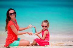 Family with sun bottle cream on white beach. Young mother applying sun cream on her kid Stock Images