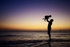 Family at sunset. Father and little daughter silhouettes on beach at sunset Stock Photography