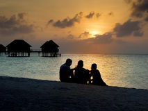 Family at sunset. Silhouette of family at sunset on vacation having a drink Stock Photos