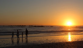 Family at sunset. A family strolling on the beach at sunset Royalty Free Stock Photos