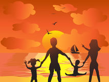 Family in the sunset beach Royalty Free Stock Image