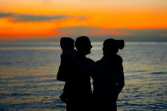 Family at sunset by the sea royalty free stock photo