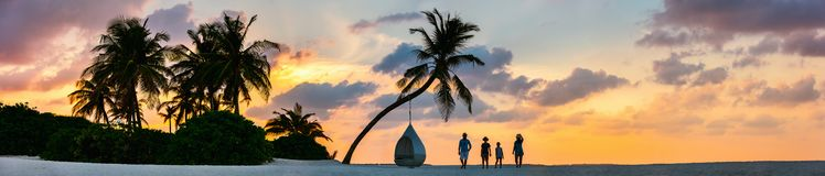 Family at sunset. Silhouettes of beautiful family of four with kids at tropical beach during sunset, panoramic photo perfect for banner Royalty Free Stock Image