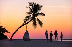 Family at sunset. Silhouettes of beautigul family pf four with kids at tropical beach during sunset Stock Image