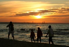 Family sunset stroll. Against, visible port cranes in background, people aren't identifable stock images
