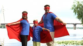 Family in superhero costumes posing for camera, togetherness and outdoor rest royalty free stock photography