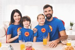 A family of superheroes sit at a table. The incredibles are posing in a bright room royalty free stock images