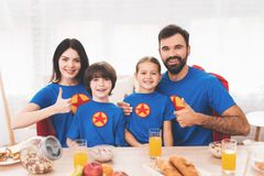 A family of superheroes sit at a table. The incredibles are posing in a bright room stock images
