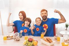 A family of superheroes sit at a table. The incredibles are posing in a bright room stock photography
