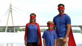 Family in superman costumes posing for camera, parental support and care concept stock images
