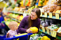 Family in supermarket. Young mother with baby daughter shopping in supermarket Royalty Free Stock Photo