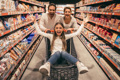 Family at the supermarket. Beautiful couple and their daughter are having fun while doing shopping in supermarket. Girl is sitting in trolley stock images