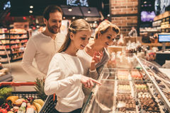Family at the supermarket. Beautiful parents and their daughter are choosing sweets and smiling while doing shopping in supermarket Royalty Free Stock Photography
