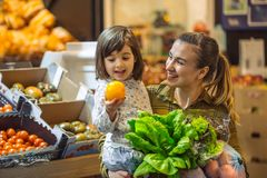 Family in the supermarket. Beautiful young mom and her little daughter smiling and buying food royalty free stock photos
