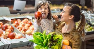 Family in the supermarket. Beautiful young mom and her little daughter smiling and buying food stock photo
