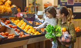 Family in the supermarket. Beautiful young mom and her little daughter smiling and buying food royalty free stock photo