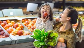 Family in the supermarket. Beautiful young mom and her little daughter smiling and buying food stock image